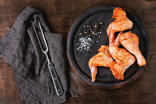 Raw Marinated chicken meat wings and legs for BBQ, served on round wood chopping board with seasoning