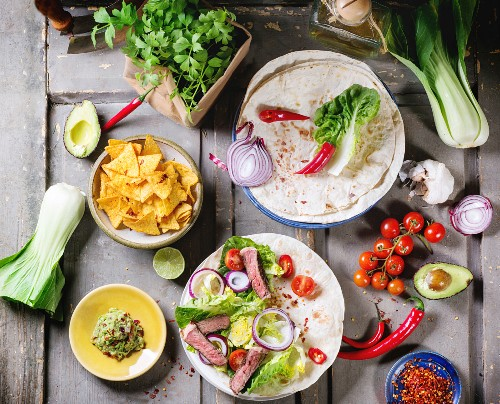 Overhead view on mexican style dinner with tacos, vegetables, nachos chips and guakomole