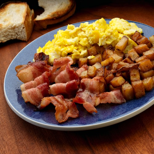 Scrambled egg with American bacon and fried potatoes