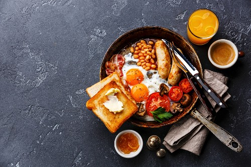 English breakfast in pan with fried eggs, sausages, bacon, beans, toasts and coffee