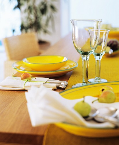 Place setting with yellow crockery glasses and cutlery in linen napkin
