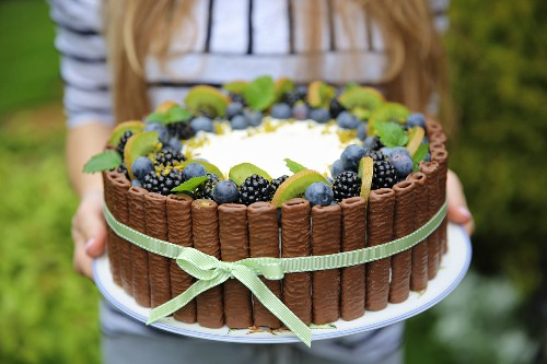 Birthday cake with whipped cream and fruits-blueberries, blackberries and kiwi
