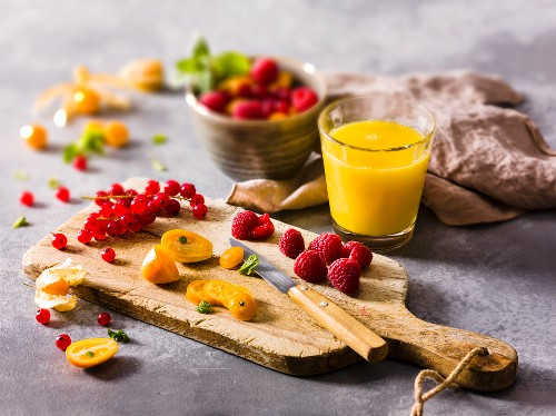 Fresh fruit on a chopping board and a glass of fruit juice