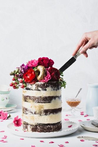 Hochzeitstorte mit frischer Blumendeko, vergoldeten Donuts und Salted Caramel Sauce anschneiden