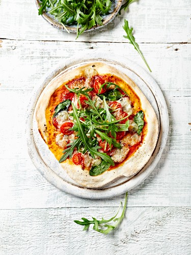 Thin Crust Pizza with Spinach, Salami and Gorgonzola topped with Fresh Arugula