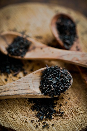 Earl Grey tea leaves on wooden spoons