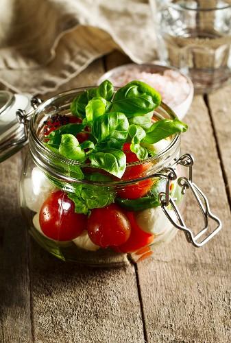 Tomato, mozzarella and basil in a glass jar