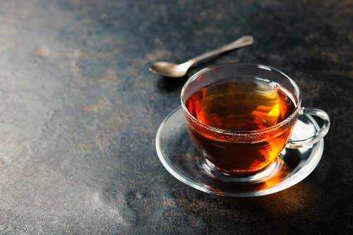 Cup with black tea on rustic metal background