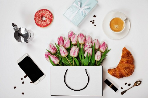 Top view of spring flowers, coffee, mobile phone, croissants, gift and cosmetics