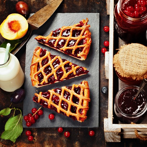 Fruit and berry jam and pieces of fruit tart on a rustic background
