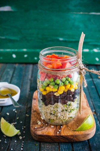 Quinoa salad with vegetables, coriander and lime vinaigrette in a glass jar