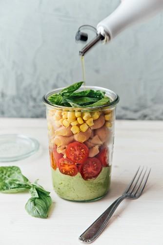 salad in a jar, avocado sauce (with garlic + basil), tomato, buckwheat and lentil pasta, corn, vegan
