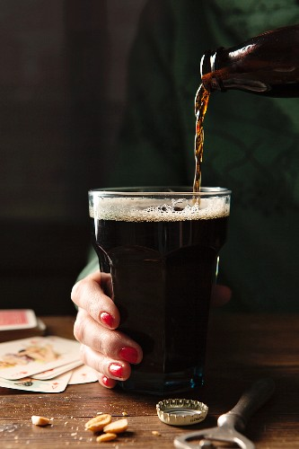 Bottle of Guinness being poured into a large glass being held by a hand with red nail varnish on a wooden table surrounds by the bottle top, bottle opener, nuts and playing cards