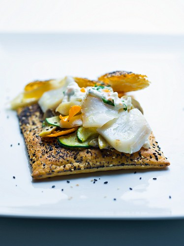 Cod and cucumber salad on puff pastry with sesame and poppy seeds