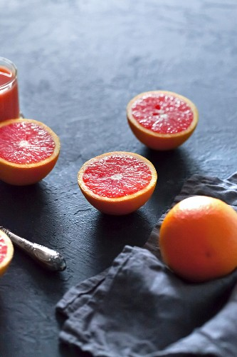 Blood oranges, whole and halved, on a grey concrete surface