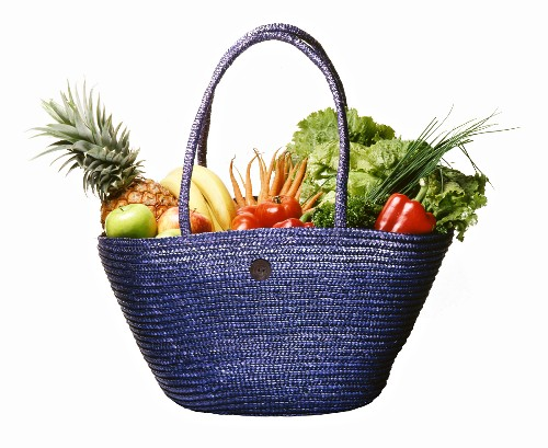 A basket of fresh fruits and vegetables against a white background