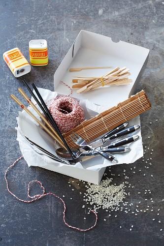 Kitchen utensils: wooden skewers, chopsticks, cutlery, kitchen string, bamboo mat