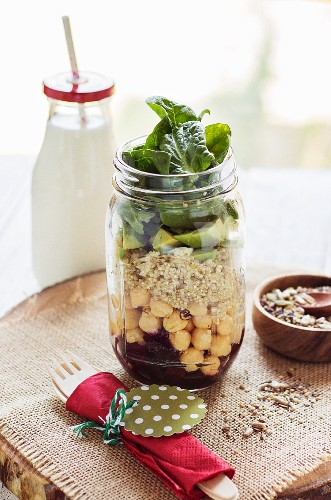 Vegan layered salad with quinoa, chickpeas and avocado in a glass jar