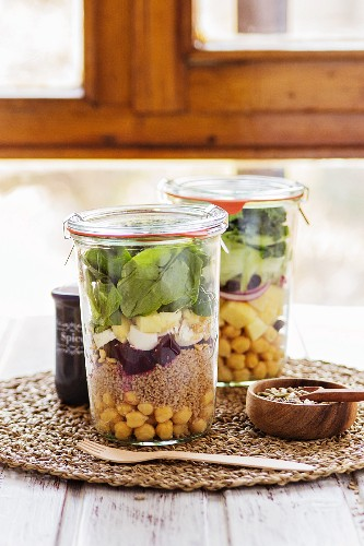 Two salads in jars prepared in a buffet service for a brunch with a mix of seeds for dressing