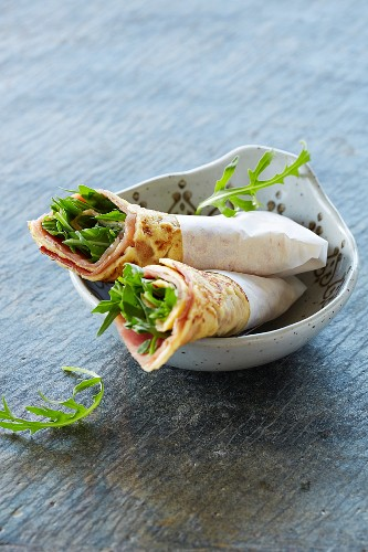 Crepe rolls with parma ham and rocket