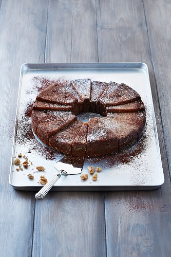 A wreath chocolate cake with nuts on a baking tray