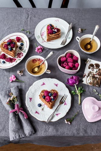A table set for Valentine's Day with waffles, berries and tea