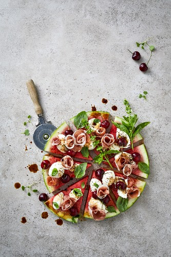 Watermelon 'pizza' with parma ham, mozzarella, cherries and basil