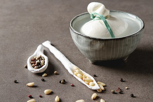 Italian fresh burrata cheese in a ceramic mousse with spices and pine nuts