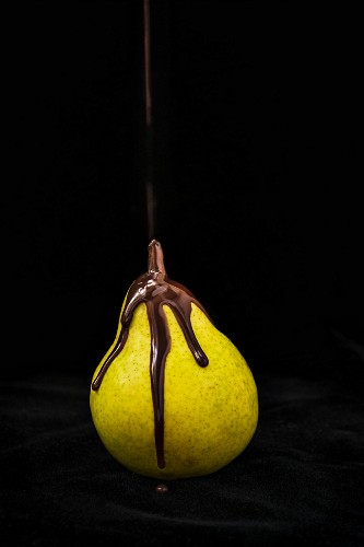 Melted chocolate flowing over a pear against a black background