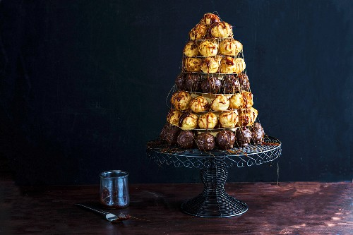 A croquembouche (a French dessert consisting of choux pastry balls bound with caramel threads) on a cake stand