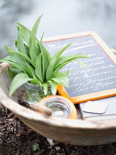 Fresh wild garlic in a glass next to a recipe chalkboard