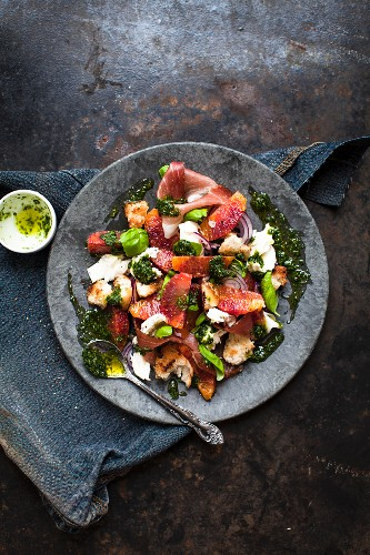 A salad with prosciutto, mozzarella, pesto, blood orange and bread