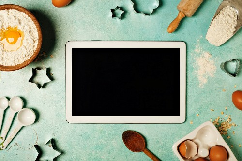 Baking background with flour, eggs, kitchen tools and tablet computer on blue rustic table