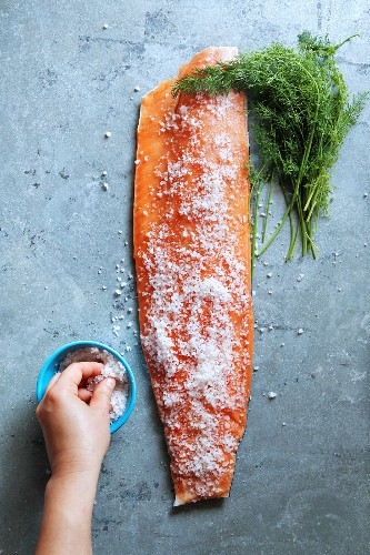 Female hand covering salmon fillet with sea salt