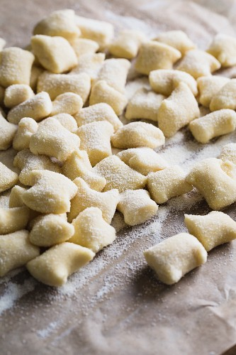 Freshly made ricotta gnocchi on baking paper dusted with semolina flour