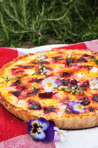 Summery beetroot quiche with feta and pansies on a picnic blanket