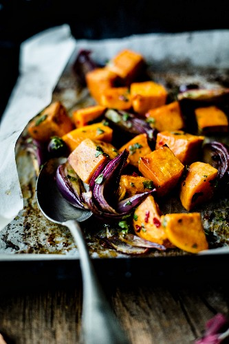 Oven roasted sweet potato cubes with red onions and herbs on an oven tray