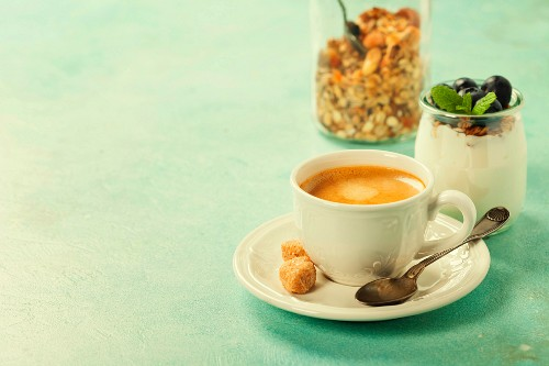 Healthy breakfast with coffee, homemade granola, yogurt and berries on blue background