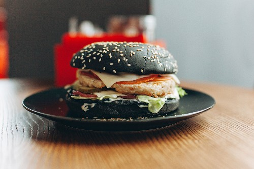 Black burger with cheese, tomatoes and lettuce