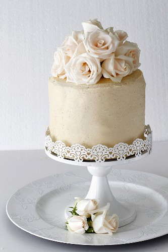A layered vanilla cake with roses on a cake stand for a special occasion