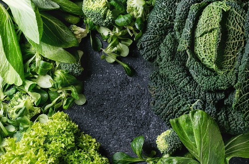 Variety of raw green vegetables salads, lettuce, bok choy, corn, broccoli, savoy cabbage