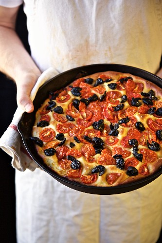 Chef holding Focaccia with Tomatoes and Olives in a iron cast pan (Italy)
