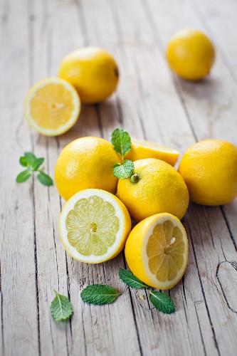 Frische Zitronen, ganz und halbiert, auf Holzbrett