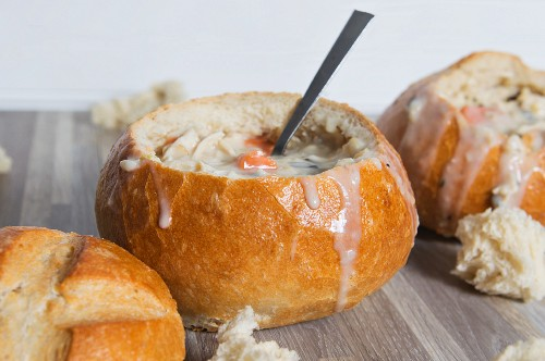 Creamy chicken soup with wild rice served in hollowed-out bread rolls