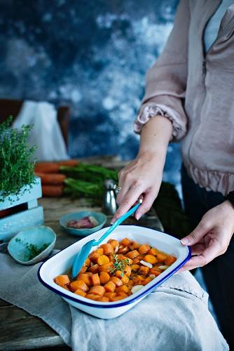 Frau beim Zubereiten von Karottengemüse