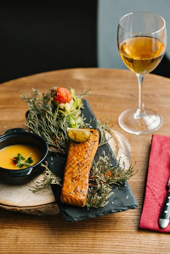 Grilled salmon on juniper branches in a restaurant