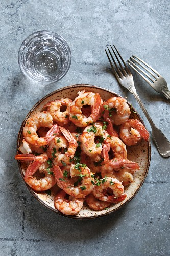 Sauteed shrimp with garlic, parsley and anchovy butter on a plat with a glass of sparkling water