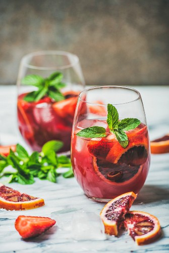 Blood orange and strawberry summer Sangria (Fruit refreshing rose wine cocktails in glasses with ice and mint leaves)