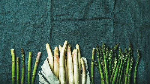Fresh green and white asparagus in towel over dark grey linen table cloth background