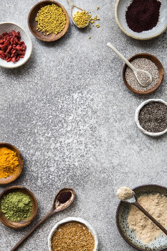 A superfood still life: bee pollen, acai, goji, chia, matcha powder, turmeric powder, flaxseed and maca